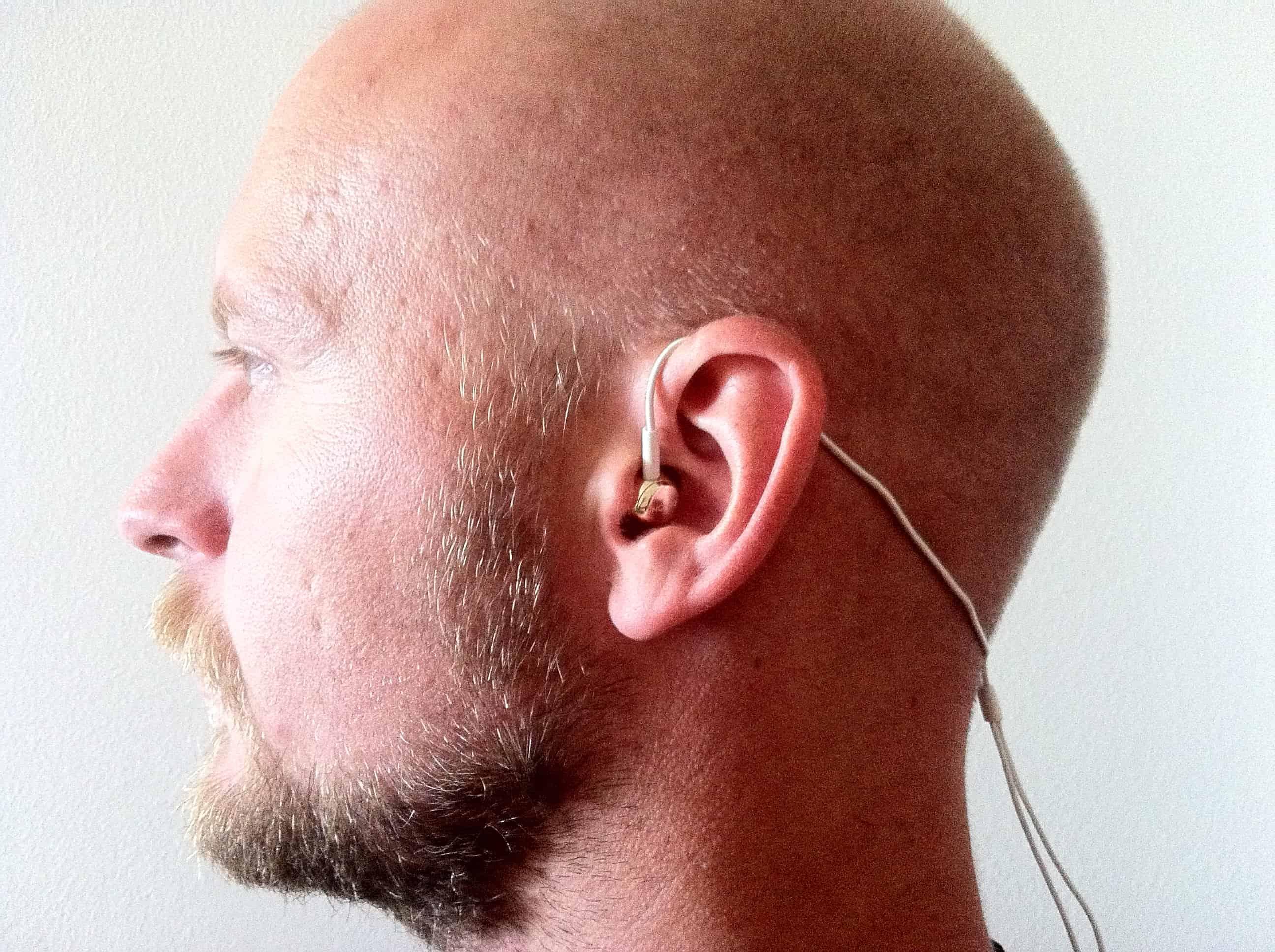Min personlige favorit. Kablet bag nakken. Høretelefonen sidder bedre og kablet er ikke i vejen. Bemærk at den omløber der er på kablet kan bruges til at stramme til bag nakken for at sikre det perfekte fit.